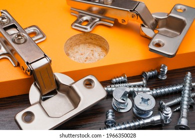 Closeup of various furniture fittings. Furniture assembly kit,  Concealed hinge and various screws on orange board.