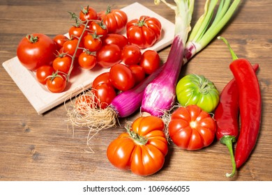 Closeup of various types of vegetables from Italy, typical of the Mediterranean diet, such as tomatoes, fresh Tropea onion (Calabria) and Sicilian spicy chili.