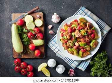 close-up of vegetable marrow Ratatouille with chicken meat served on a white plate on a concrete table with ingredients, horizontal view from above