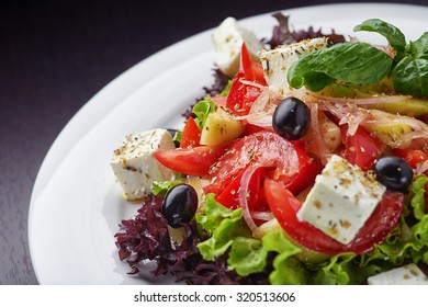 Closeup of vegetable salad on white plate and black background