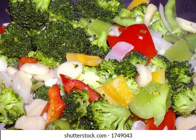 Closeup of a vegetable stir fry including broccoli, red peppers, yellow peppers, green peppers, white onions, water chestnuts, and garlic