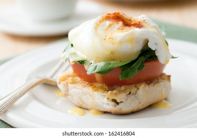 Closeup of vegetarian eggs benedict (eggs florentine) with fresh tomato and spinach.