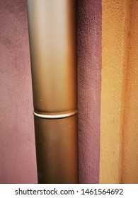 closeup of vertical copper coloured large pipe against purple and orange painted wall