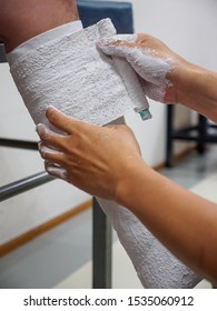 Closeup vertical detail of a physician wrapping Plaster of Paris bandages around a patient's fractured leg to make an orthopedic cast. Healthcare and sports medicine.