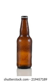 Closeup vertical image of a single unopened cold brown beer bottle covered with dew on white with reflection