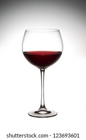 Close-up vertical shot of wine in wine glass against white background.