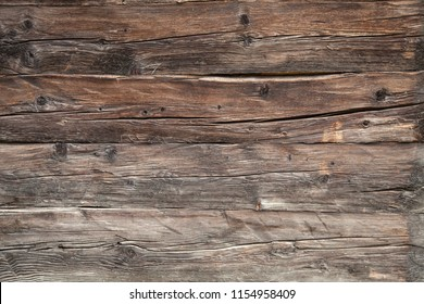 closeup of very old grungy brown wooden weathered planks of door or barn
