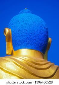 Closeup vibrant blue Shanti Ban Buddha head, 25 feet tall golden Buddha's image on a sunny day in Dhulikhel, Nepal