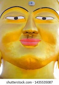 Closeup vibrant gold Shanti Ban Buddha face, 25 feet tall golden Buddha's image on a sunny day in Dhulikhel, Nepal