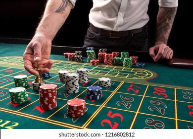A close-up vibrant image of green casino table with roulette, with the hands of croupier and multicolored chips.