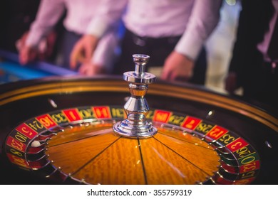 A close-up vibrant image of multicolored casino table with poker chips and roulette in motion, with the hand of croupier, and a group of gambling rich wealthy people in the background