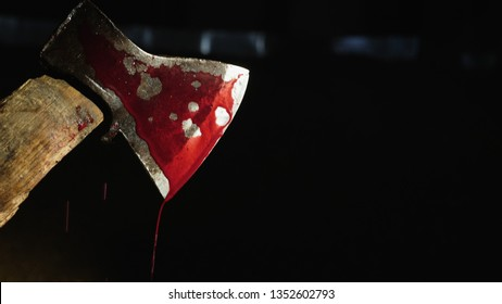 Closeup video: Axe with blood in hand on the dark background. Drops of blood flow down the blade of an ax. Murderer or butcher, halloween theme