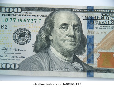 Close-up view of a 100 dollar banknote on a white background. Benjamin Franklin.