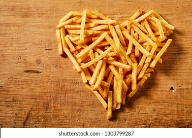 Close-up view from above of a heart shape made of tasty French fries served on a wooden rustic table as concept for love or fast food