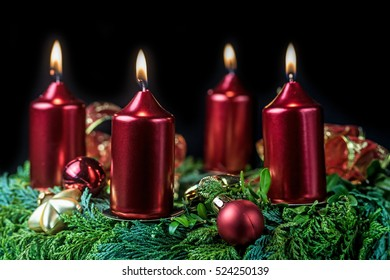 Closeup view of the Advent wreath with four red shining candles on a black background. Horizontally.
