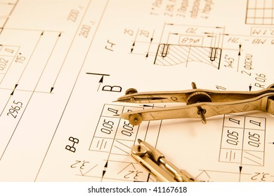 A closeup view of an architect's drafting table showing a blueprint and two compasses