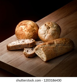 Closeup view of arrangement of assortment of baked bread in a dark ambiance