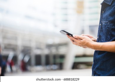 Close-up view of an Asian businessman using digital smart phone in the city