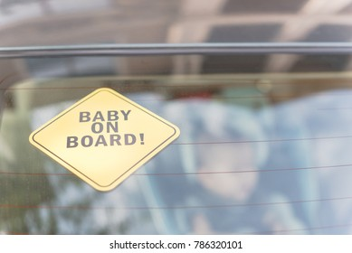 Close-up view of Baby On Board sticker on the car back windows. A blurred image of car seat is available in background.