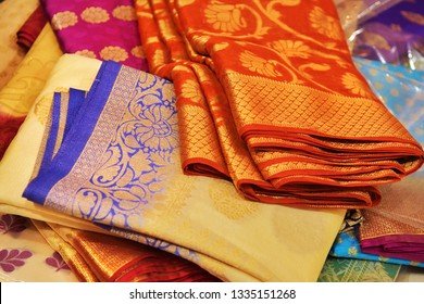 Closeup view of Banares silk saris in a textile shop,  displayed in front of customers. These exquisite, expensive sarees are famous for their gold and silver zari, brocade. Incredible India.