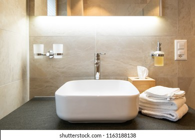 Close-up view of bathroom sink , shelf, towels and soap dispenser.
