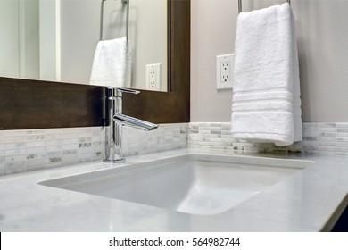 Close-up view of bathroom vanity cabinet topped with white and grey counter paired with tile backsplash under framed mirror. Northwest, USA Northwest, USA