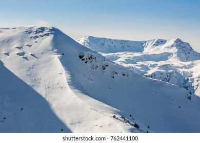 Close-up view of the beautiful Alpine mountains covered by snow on a sunny winter day