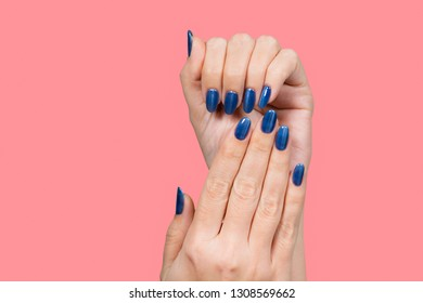 Closeup view of beautiful female hands with blue glossy professional manicure isolated on pink background. Horizontal color photography.