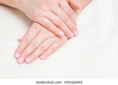 Closeup view of beautiful female hands on towel. Beautiful female hands  on towel. Hand care. Woman cares for the nails on hands. Beauty treatment with skin of hand.