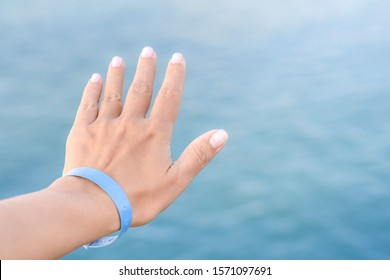 Closeup view of beautiful white female hand wearing blue rubber wristband. Hand isolated at blurry sea water bokeh background. Happy travel and all inclusive system of hotel resorts concept.