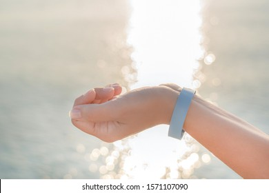 Closeup view of beautiful white female hand wearing blue rubber wristband. Hand isolated at blurry sea sunny water bokeh background. Happy travel and all inclusive system of hotel resorts concept.