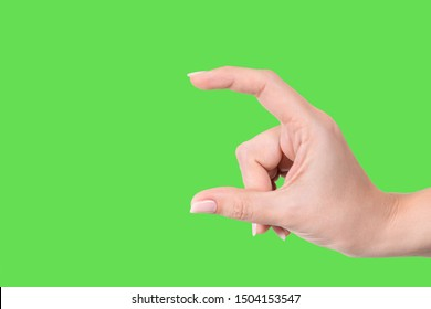 Closeup view of beautiful white manicured female hand showing size of virtual invisible object with help of two fingers isolated on green background. Horizontal color photography.