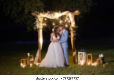 Closeup view of beautiful young couple in love at their happy wedding. Bride and groom standing together at charming place during their wedding ceremony at night. Blurry unrecognizable people.