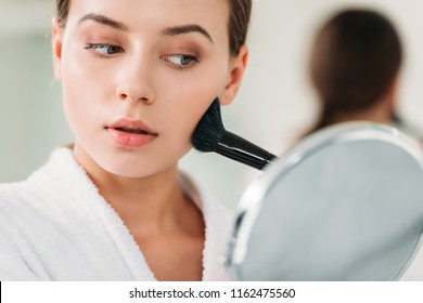 close-up view of beautiful young woman in bathrobe applying makeup