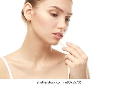 Closeup view of beautiful young woman applying lipstick, white background