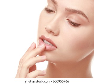Closeup view of beautiful young woman with natural makeup touching lips on white background