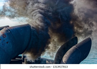Close-up view of black exhaust fumes coming from the chimney of an moored vessel after main engine ignition.