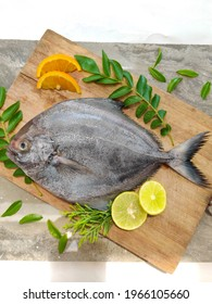 Closeup view of black pomfret fish decorated with fruits and herbs on a wooden background,Selective focus.