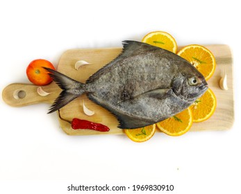 Closeup view of black pomfret fish decorated with fruits and herbs on a wooden pad,white background,Selective focus.