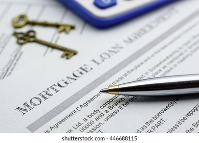 Closeup view of a blue ballpoint pen, a calculator, two vintage brass keys and a mortgage loan agreement on a table. A form is waiting to be checked and reviewed by a homeowner or a borrower.