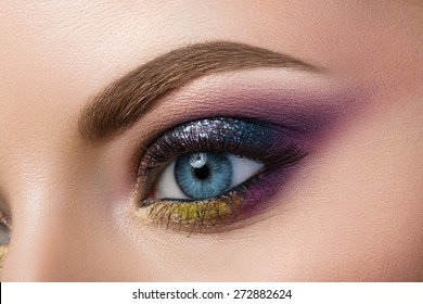 Close-up view of blue female eye with beautiful modern creative make-up