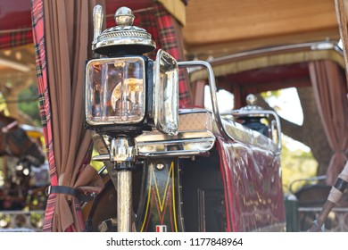 Close-up view of brass candle powered headlamp on a horse drawn carriage.