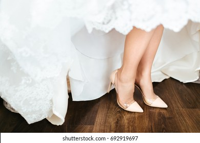 Close-up view of bridal beige shoes stands on a wooden floor.