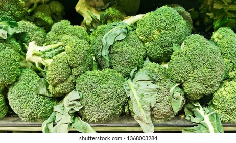 Close-up view of broccoli on supermarket shelf with leaves