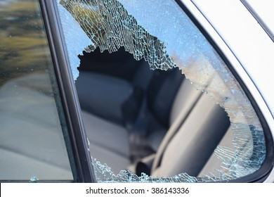 Close-up view of a broken passenger window car smashed by a thief. Damaged glass from car theft.
