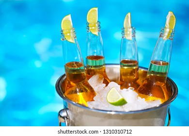 Closeup view of bucket with ice cubes, beer bottles and lime slices by the pool