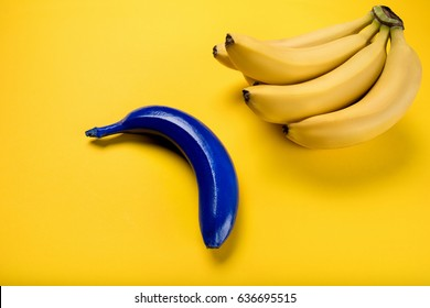 Close-up view of bunch of fresh ripe bananas and blue one isolated on yellow