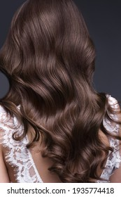 A closeup view of a bunch of shiny curls brown hair