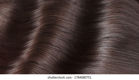 A closeup view of a bunch of shiny straight brown hair in a wavy curved style. - Shutterstock ID 1784080751