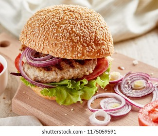 Close-up view of burger on wooden board with onion and tomatoes